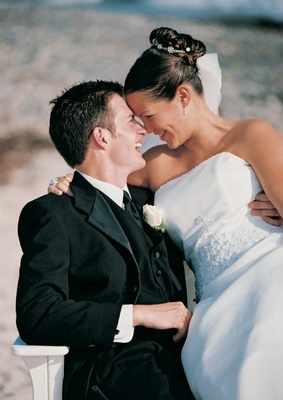 Bride and groom touch foreheads on sand
