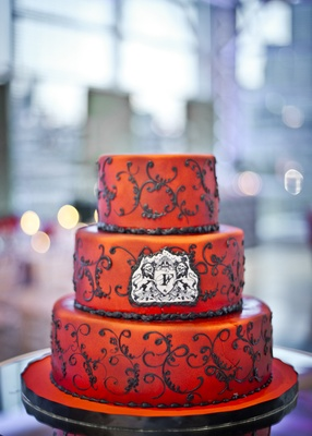 three tiered cake with red airbrushed fondant and black scrollwork