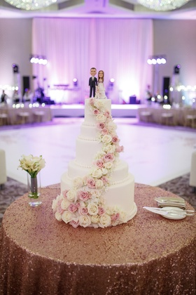 five-tier white wedding cake with pink and white roses