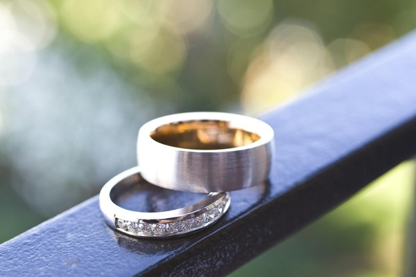 Bride's brushed gold wedding band with diamonds and groom's wedding band