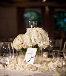 Small centerpieces with white roses and candles flower petals on tables