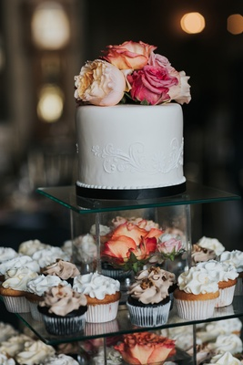 mini wedding cake with cupcakes displayed