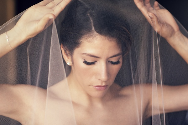 Bride putting mantilla veil over head and face