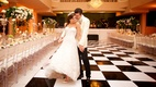 bride and groom hold each other on black and white checkered dance floor in reception space