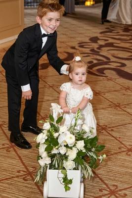Ring bearer in small tuxedo with flower girl pushing flower cart at hotel Ritz Carlton