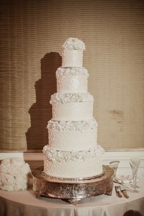 Wedding cake white with design and monogram with fresh flowers alternating each layer