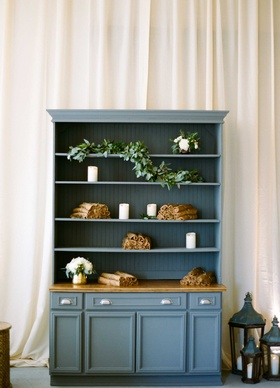 Blue shelf with tan pashmina blankets and candles eucalyptus garlands at wedding reception