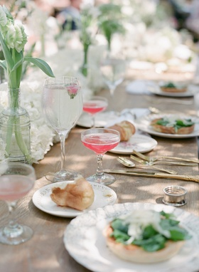 Rustic wood reception table with hydrangea runner and breakfast food