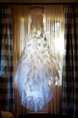 Bridal gown hanging in bridal suite with sun shining through