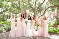 bride in vera wang and bridesmaids in pink amsale dresses hold bouquets in the air