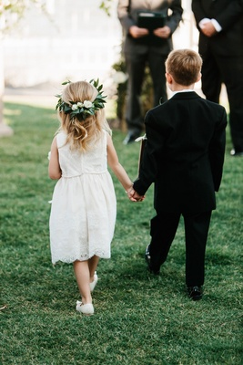 White flower girl dress with leaf flower crown holding hands with ring bearer in tuxedo suit grass