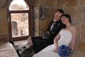 Groom in kilt with bride inside Scottish castle
