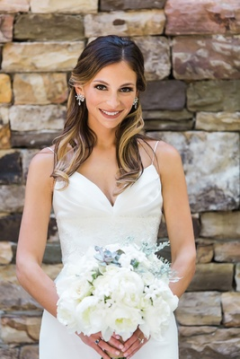 Bride in wedding dress from Bella Bianca Bridal Couture long hair curled highlights earrings