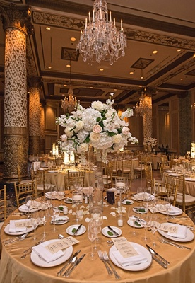 gold table linens white china charger plates tall glass vases ivory and blush floral arrangements