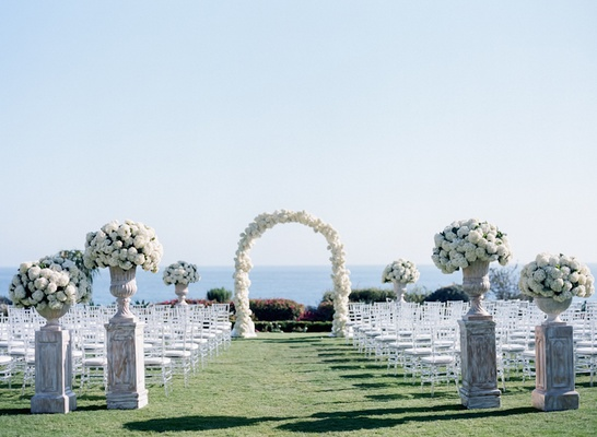 Wedding ceremony with urns of white hydrangeas, white floral arch on lawn of Montage Laguna Beach