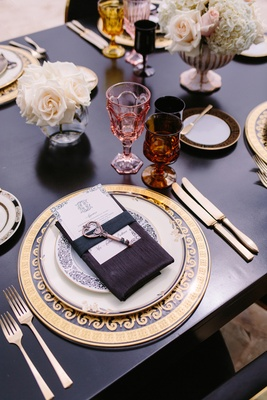 ornate clear and gold charger, black table and linens, key on menu