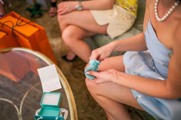 Bride to be at bridal shower opening Tiffany & Co. gift from blue box