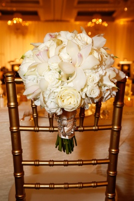 Bride's bouquet of white roses, hydrangeas, orchids, calla lilies bound with pink ribbon, rosary