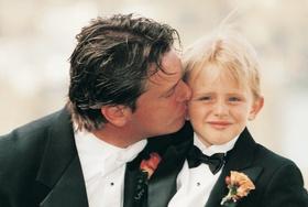 Groom kisses young ring bearer son on cheek