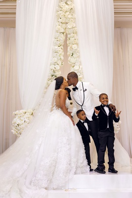 shannon perkins tahir whitehead kiss at wedding ceremony with sons at altar on stage cute family