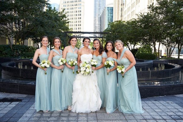 bride in white tulle gown and bridesmaids in long teal dresses differing necklines white bouquets