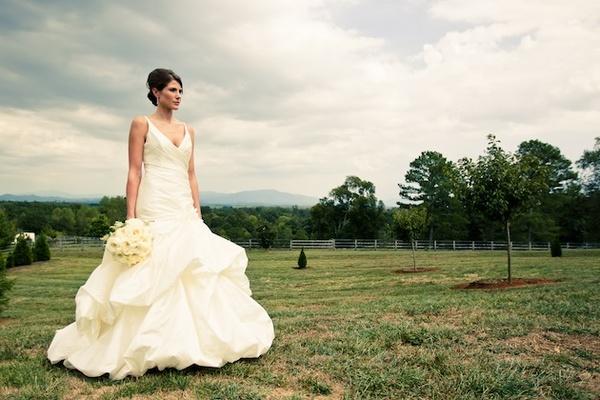 Bride wearing sleeveless wedding dress in field