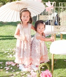 Outdoor wedding with two flower girls in sleeveless blush dresses, rosette skirts, ribbon sashes