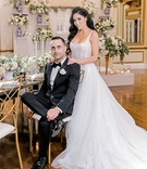 wedding portrait of bride and groom in reception ballroom blue and white decor greenery gold details