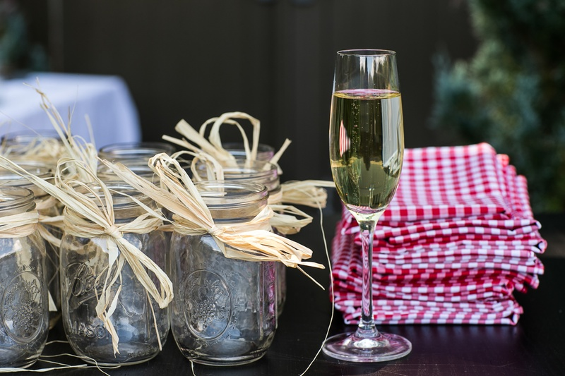 champagne glass with gingham napkins and mason jars with raffia