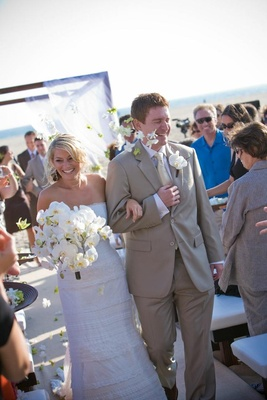 Bride and groom walk up aisle at beach wedding ceremony
