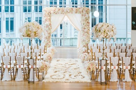 Wedding ceremony with city views and white, blush decor, wood floor with white petals