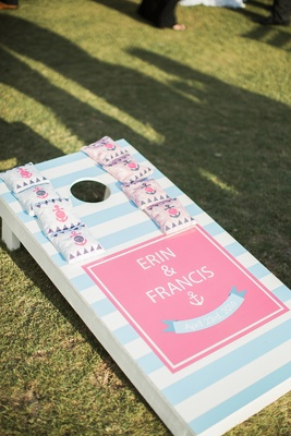 baby blue and white striped corn hole with pink square and names with anchor and bean bags