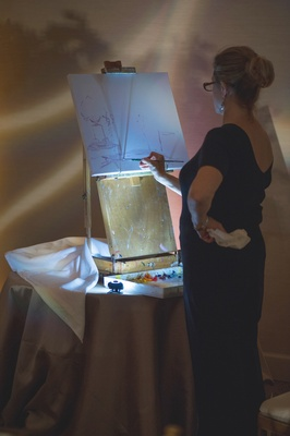 Female artist in a black dress painting the scene of a reception on a canvas