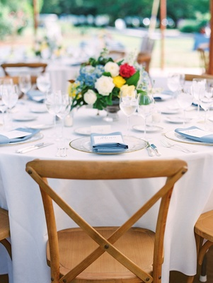Wedding reception round table white linen blue napkin low centerpiece yellow white blue red flowers