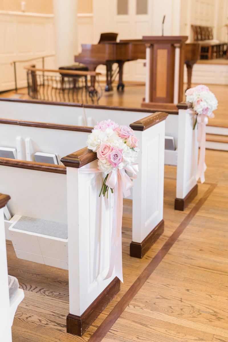 ivory and pink flowers displayed on pews at church ceremony