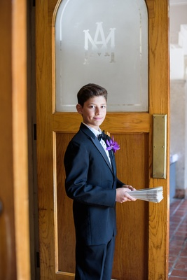 young usher with purple boutonniere with ceremony programs at catholic wedding