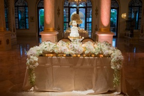 Wedding reception sweetheart table with white flower garland runner and gold linen