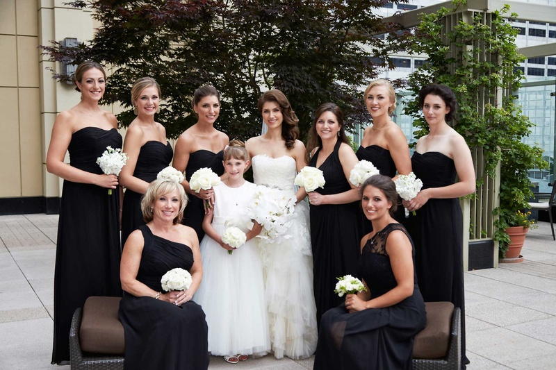 bride and bridesmaids in black dresses with white orchid bouquets flower girl in white dress