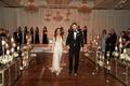 Bride in Inbal Dror wedding dress holding groom's hand tuxedo mirror ceremony decor chandeliers