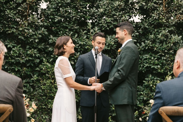 bride in short sleeve givenchy wedding dress groom with officiant in front of hedge wall outdoor