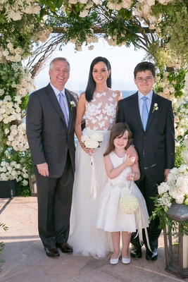 Bride in butterfly applique wedding dress with daughter and son vow renewal husband under arch