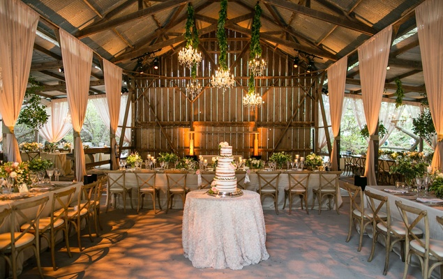 Naked Cake In Center Of Barn Open Side Venue With Drapery Chandeliers Wood Beams Chairs