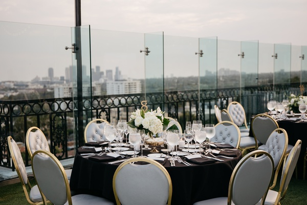 rooftop wedding reception, grey tufted chair cushions with gold frames, black linens