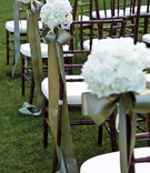 Wedding ceremony chairs with green ribbon and white flowers