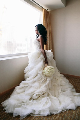 Lazaro bridal gown with ruffled skirt and bouquet