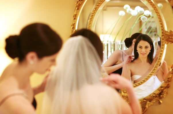 Bride gets ready in front of a gold-rimmed mirror