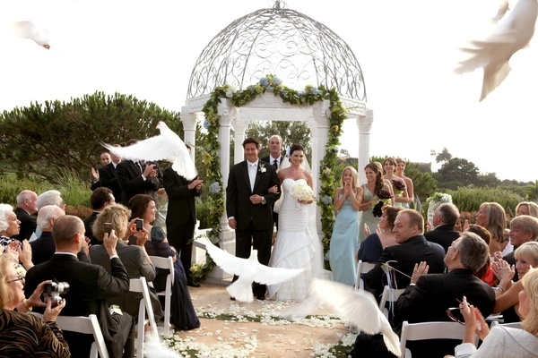 Bride and groom recessional with doves flying