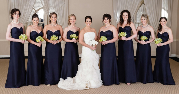 Bridesmaids in floor-length dresses holding nosegays