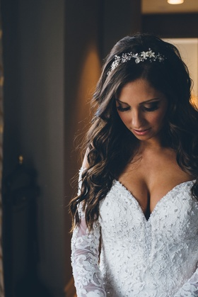 Bride in low cut lace wedding dress embellished long sleeves headpiece long brown hair