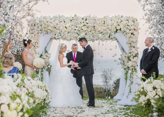 lush ceremony arch with lots of white flowers and drapery